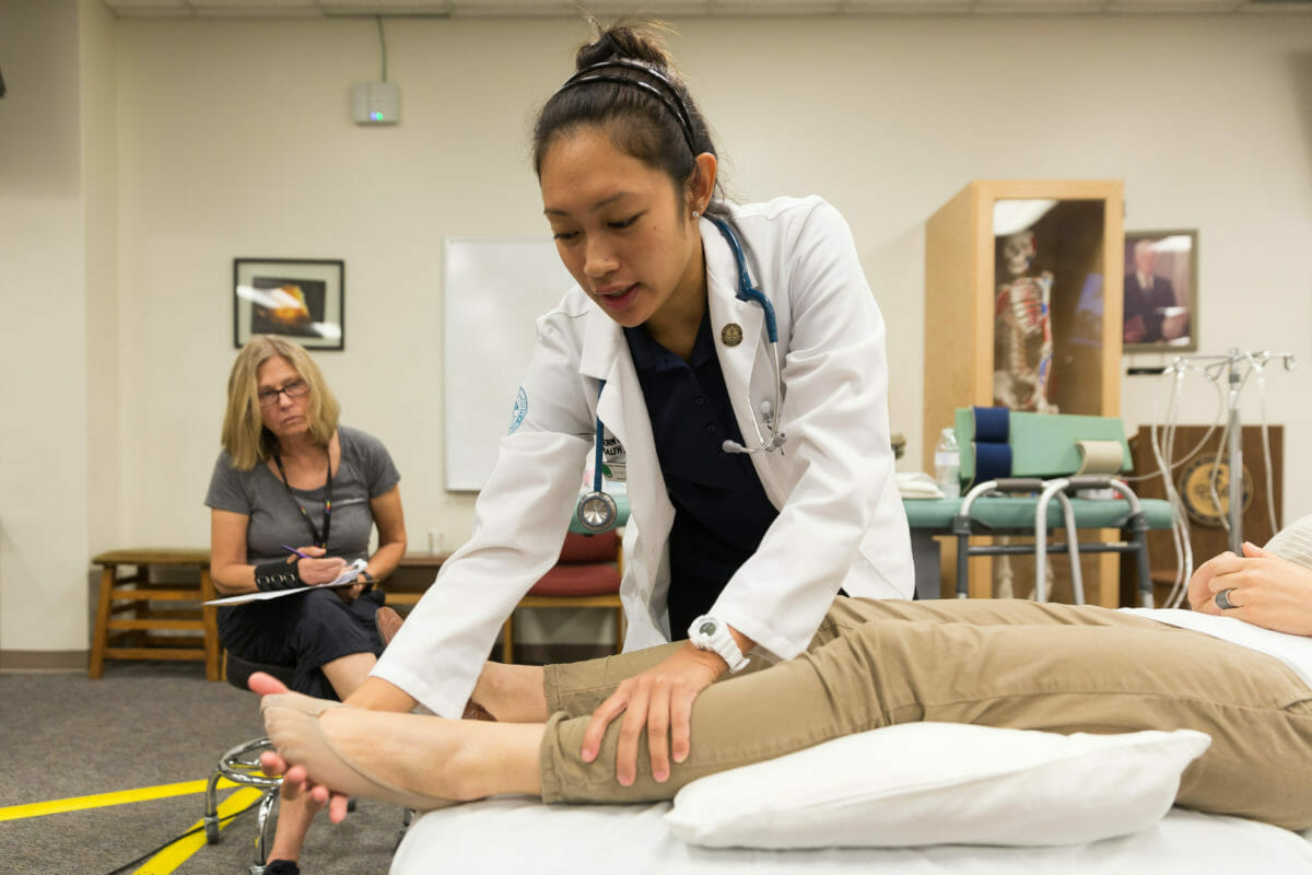 Student working with patient's legs